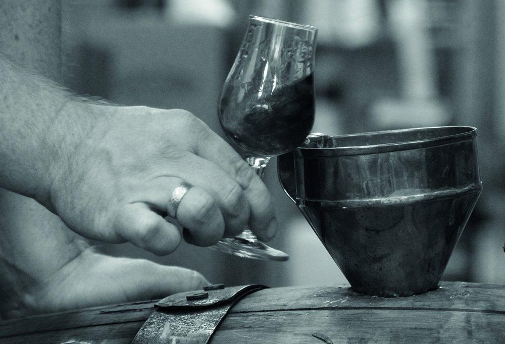 Destlleri et glas i hånden ved en tønde